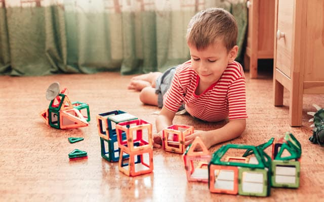 Boy playing with some of the best magnetic tile toys