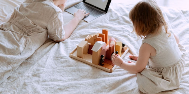 Toddler playing with educational toy while mother is working online