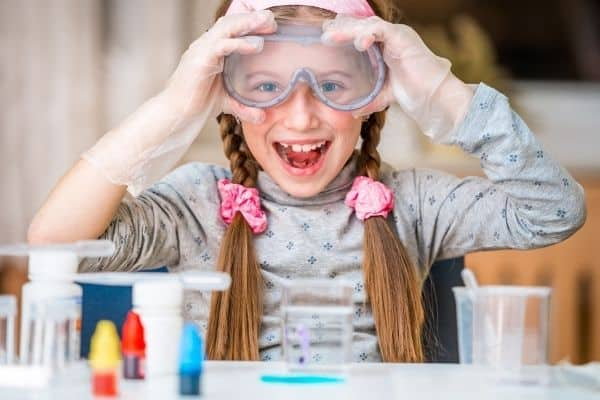 Young girl wearing protective glasses in preparation for chemistry experiment