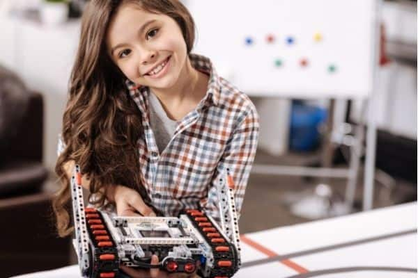 Young girl showing electronic robot car toy as STEM gift