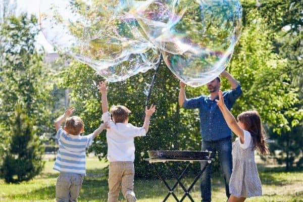 Dad and kids playing with big bubbles outdoors