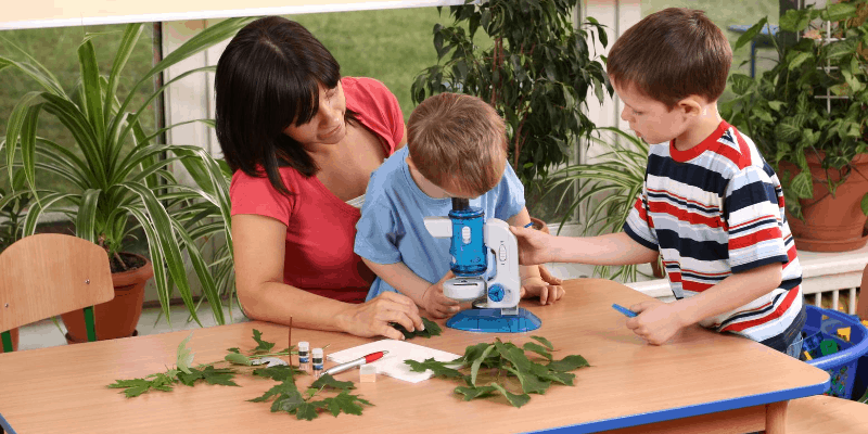 Mother teaching children how to use a microscope
