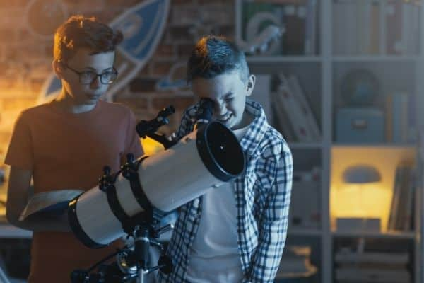 Children using mounted telescope at home for night sky viewing