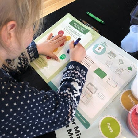 Toddler filling in a science lab book from the colorful chemistry kit