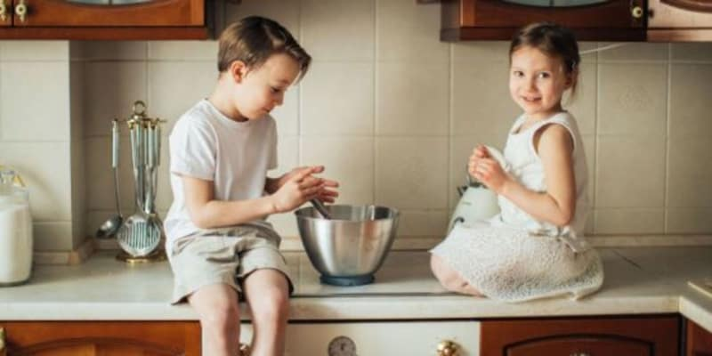 little boy and girl helping to bake or cook