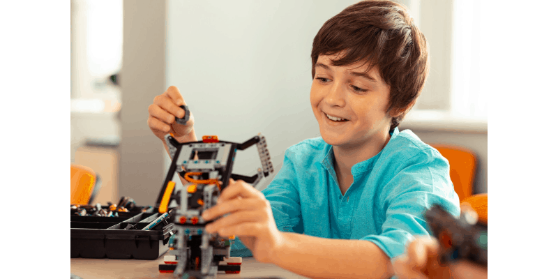 young boy building a cool robot toy