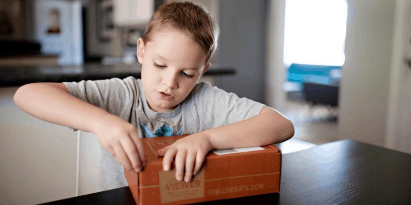 Young boy happily opening a Tinker Crate STEM box