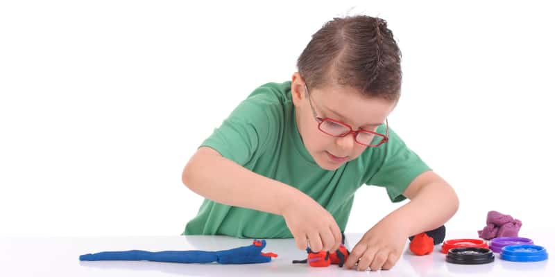 Child shaping Play Doh to create a circuit