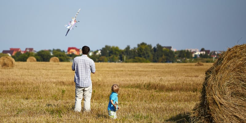 Father and child playing with remote control plane in the field