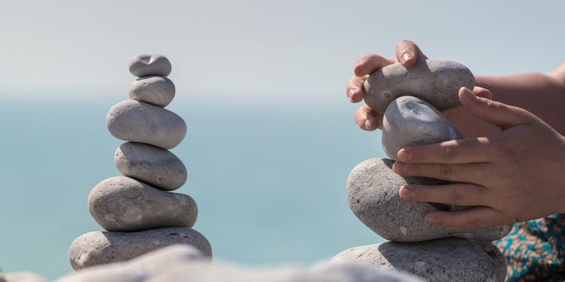 Hands balancing rocks to build a stone tower