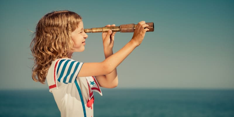 Little girl using a telescope for land viewing