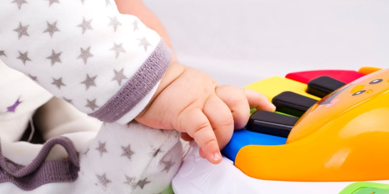 Infant playing with colorful piano toy