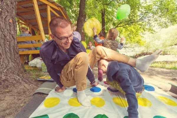 Kids and adult playing twister game outdoors