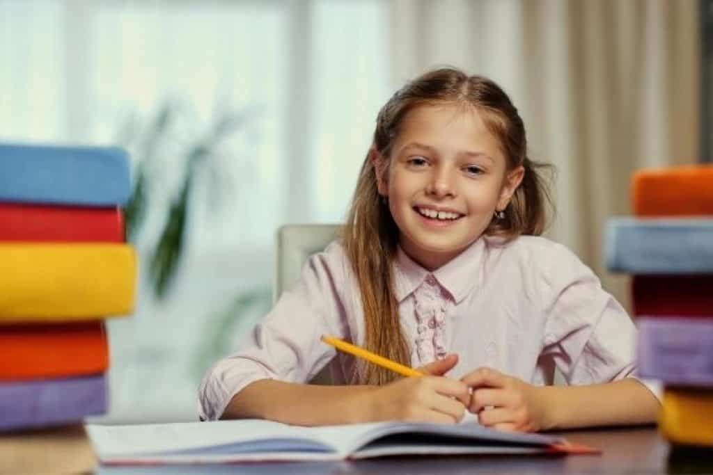Middle school girl with books on table