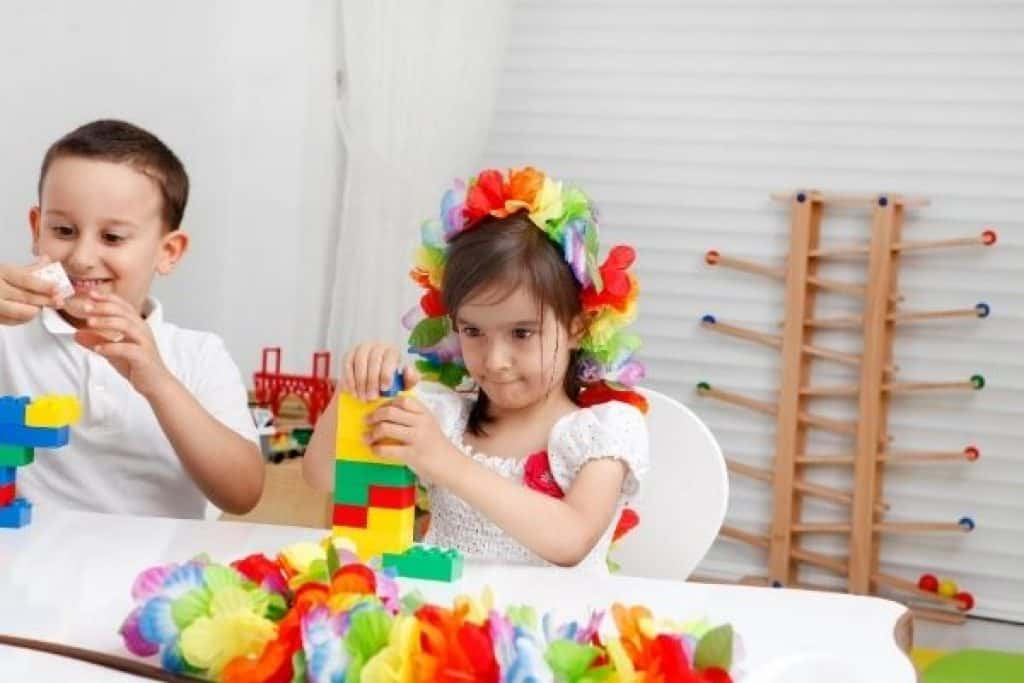 Preschool girl playing with colorful building blocks