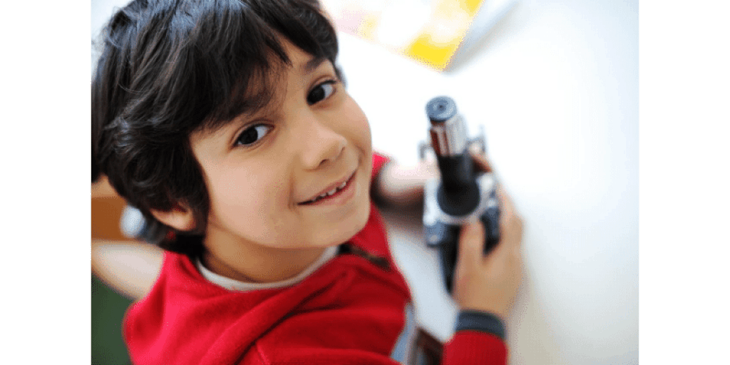 Young boy holding microscope for homeschool
