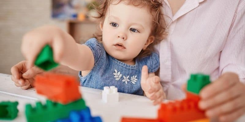Mother and daughter playing with building toy