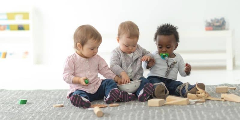 Toddlers playing with wooden blocks
