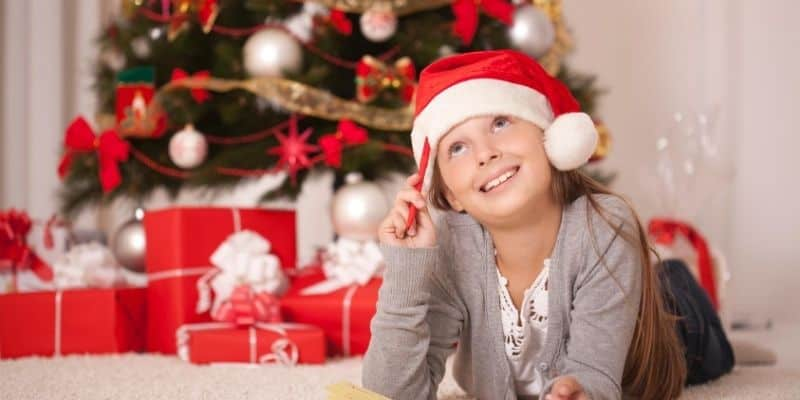 Child writing a hidden message on Christmas card