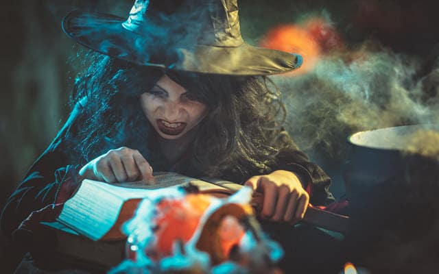 Ingredients for homebrew DnD - a Witch poring over her speelbook near a cauldron