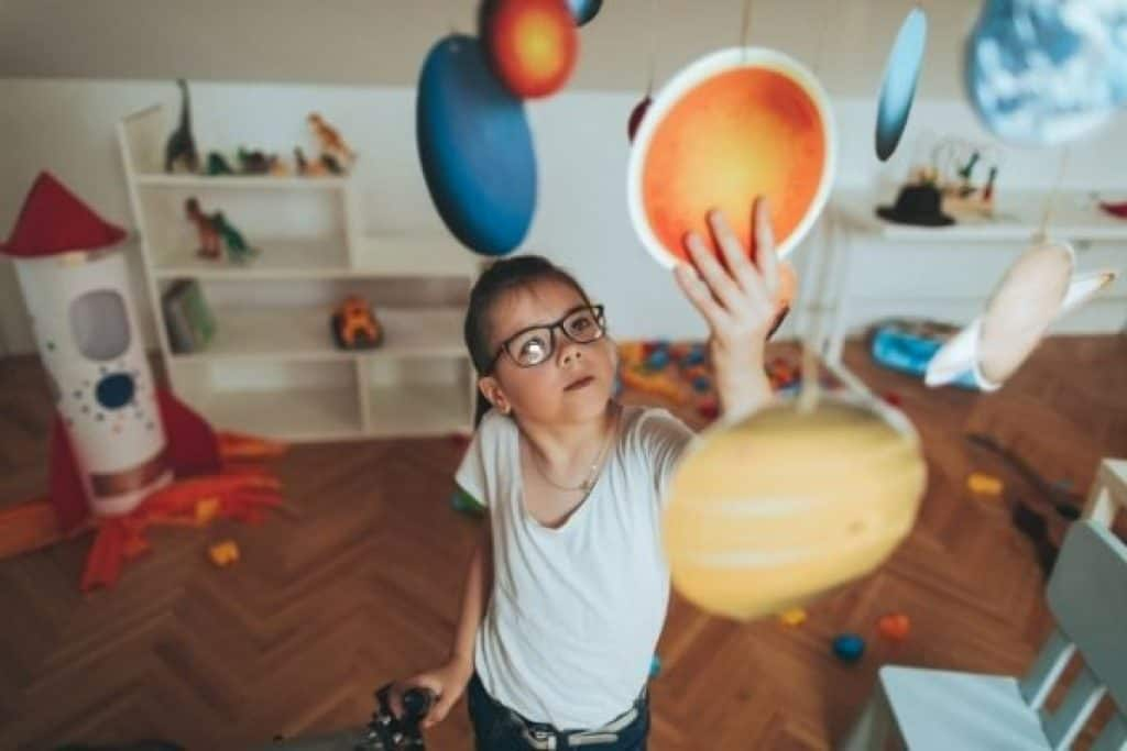 Child looking at mobile solar system model