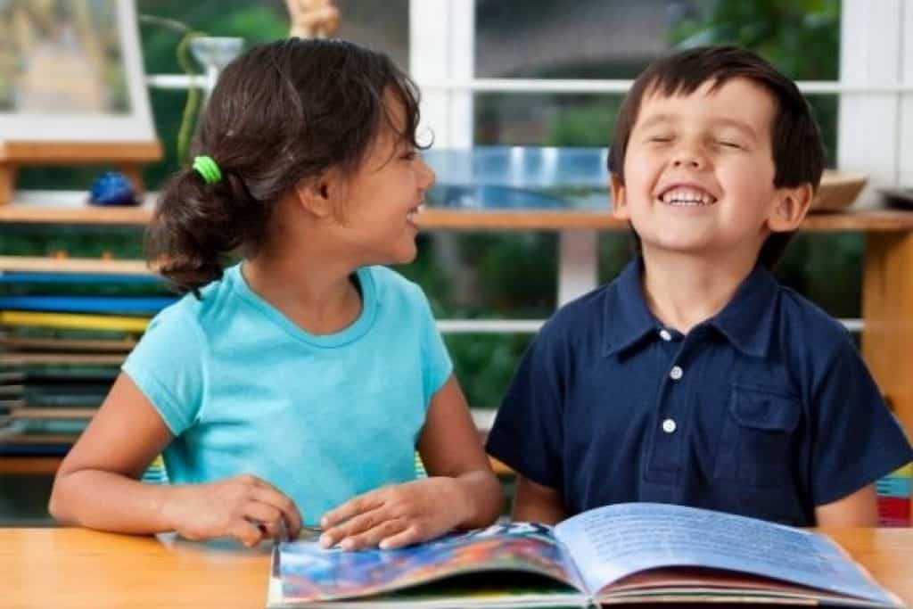 Preschoolers laughing while reading an Usborne book
