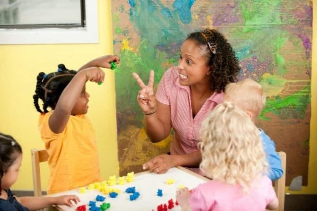 Teacher and preschoolers playing a board game