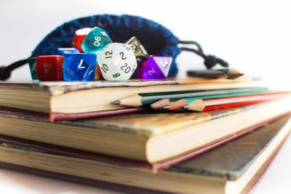 Reference books for dungeons and dragons with dice and pencil on top