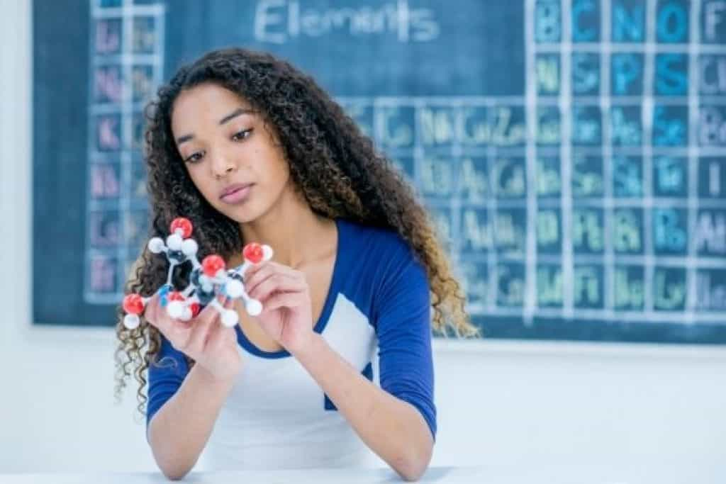 Woman holding molecular model with blackboard on the back