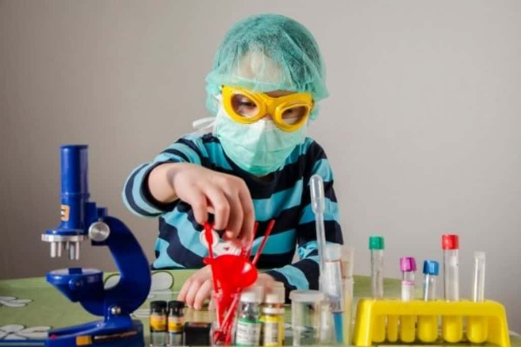 Child wearing safety equipment for chemistry experiment