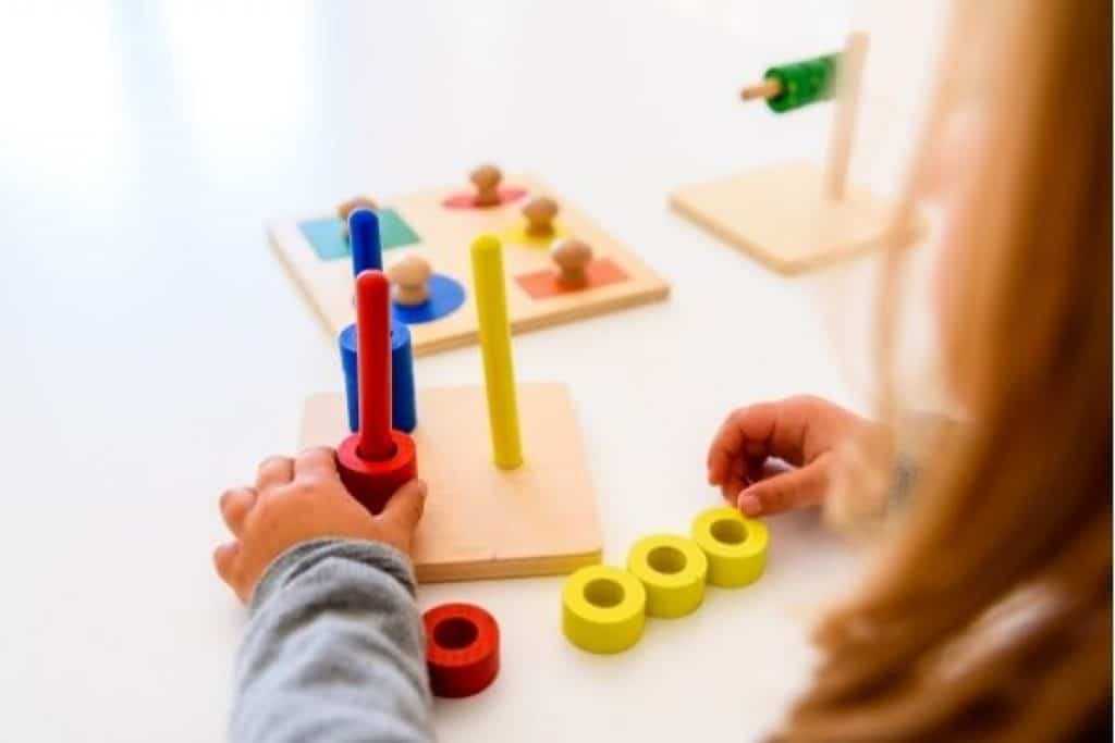 Kid playing with educational wooden toy