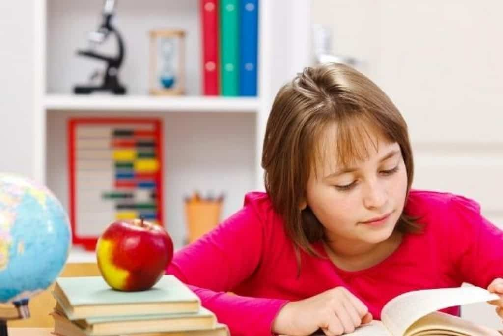 Young girl in middle school reading a book