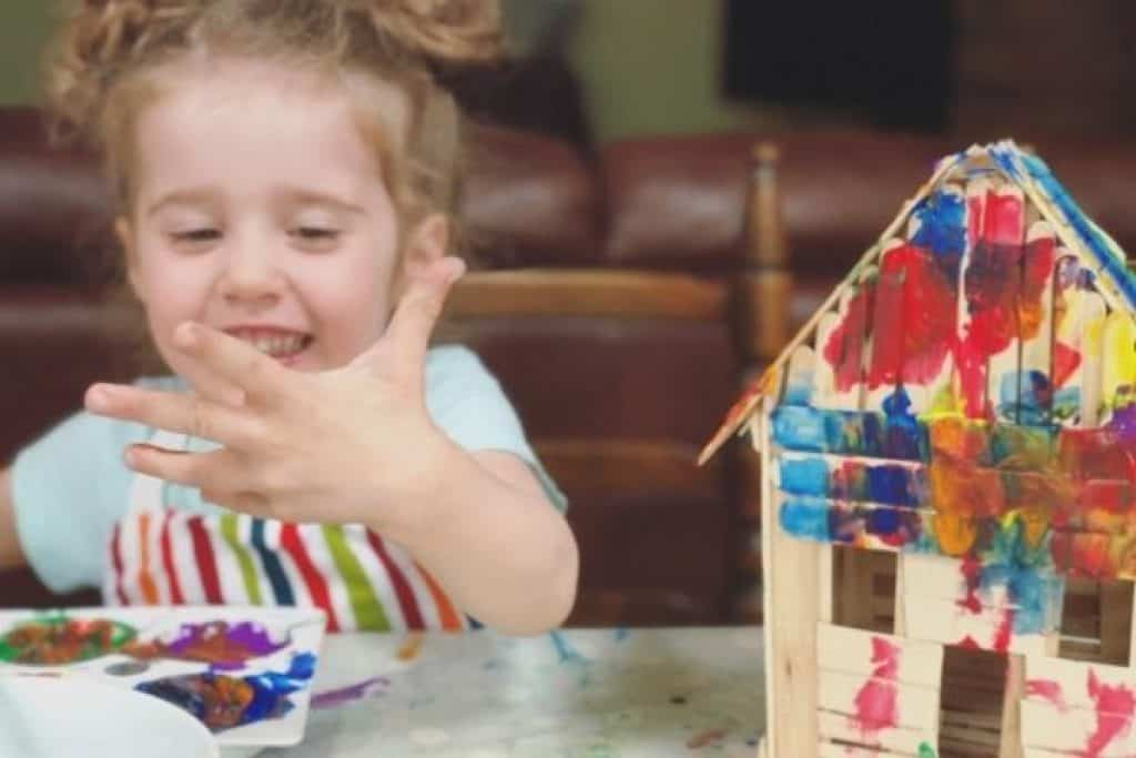 Kid doing crafts with colors and wooden sticks