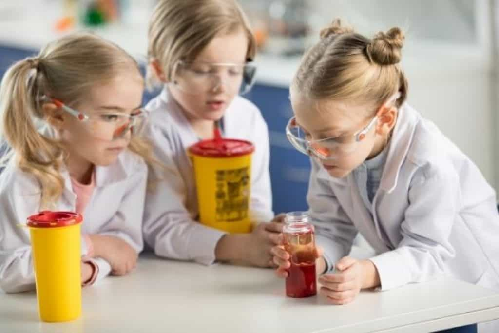 Children in lab coats doing science experiment