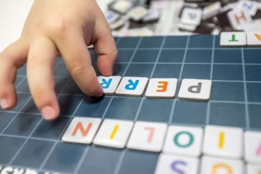 Child playing with magnetic alphabet board toy