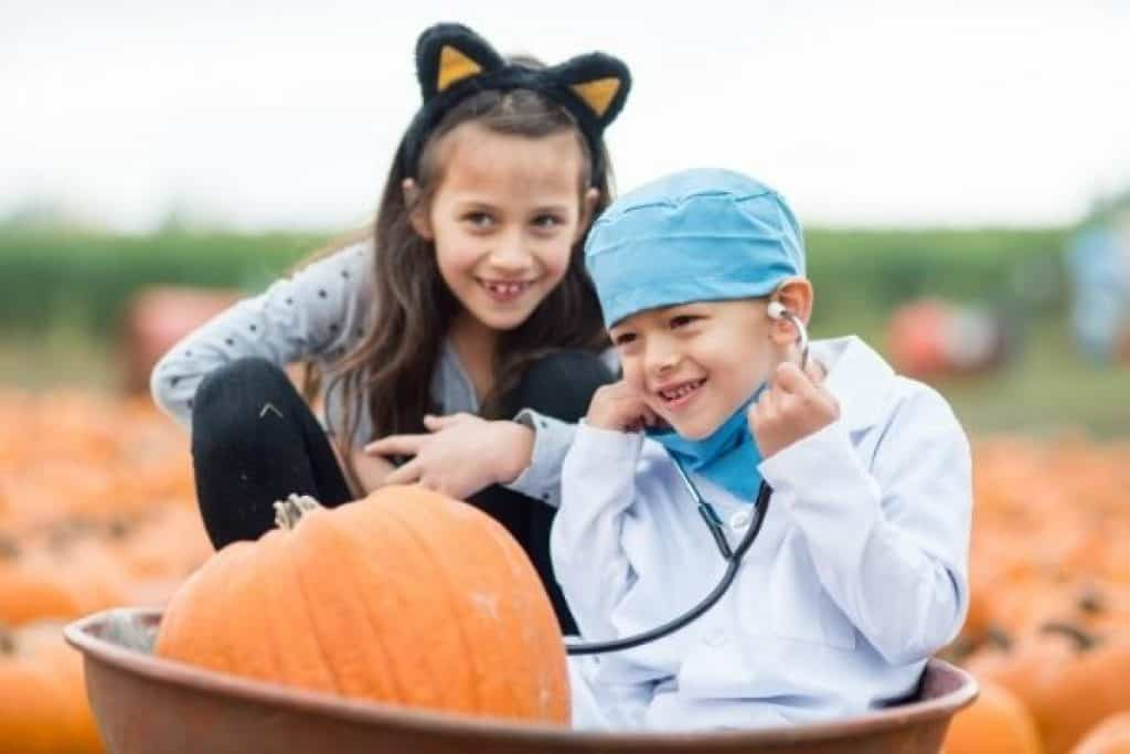 Children in scifi costumes surrounded by pumpkins