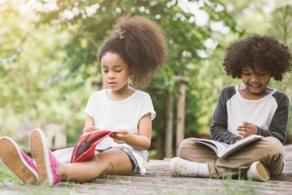 Young girls reading books outdoors