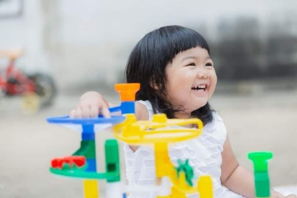 Young girl happily playing with colorful learning toy