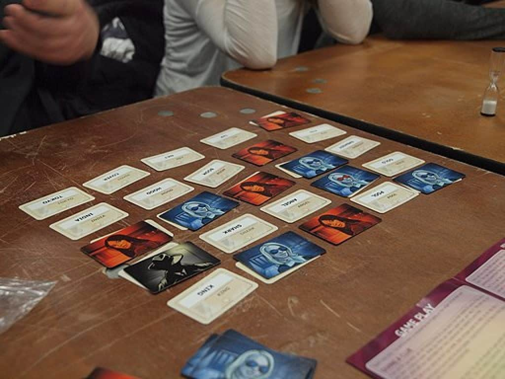 People playing Codenames board game