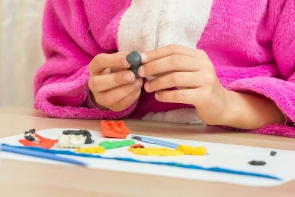 Child playing with clay craft kit