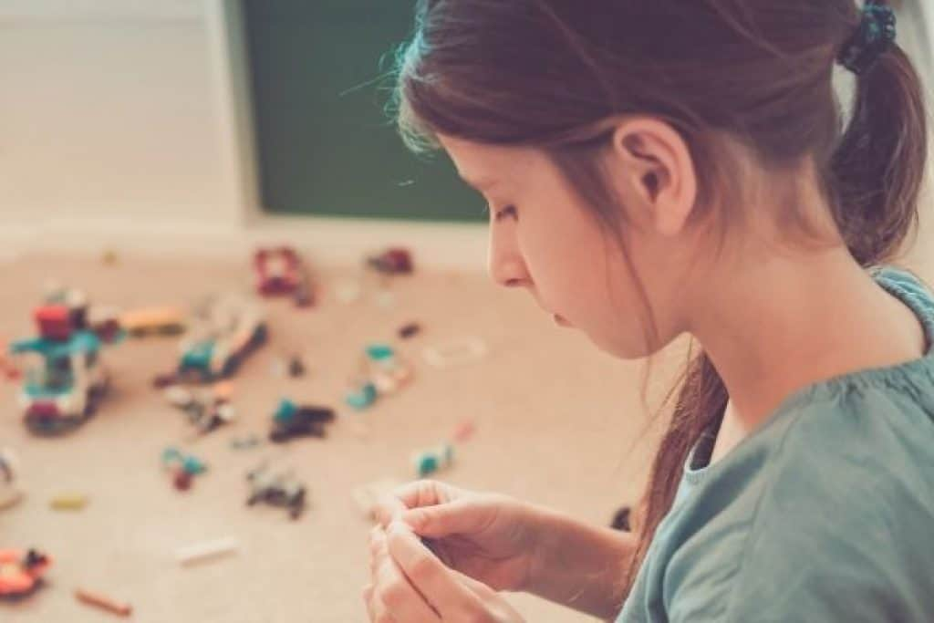Young girl playing with LEGO set