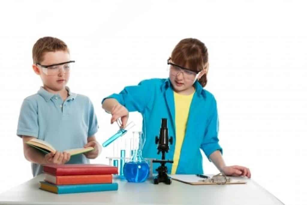 Kids with science books doing experiments