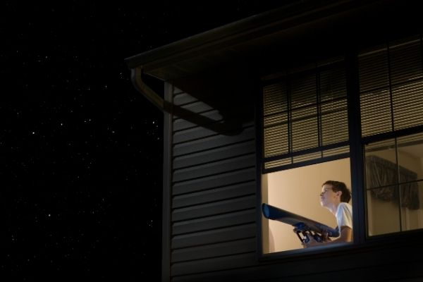 Teenager in bedroom holding a telescope to view the sky at night