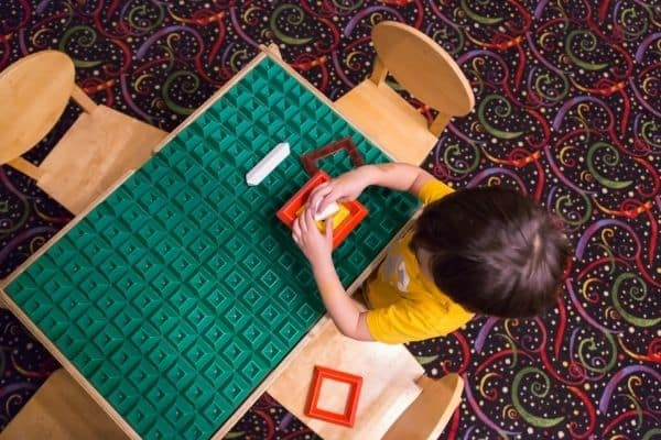 Kid playing with colorful shape toys