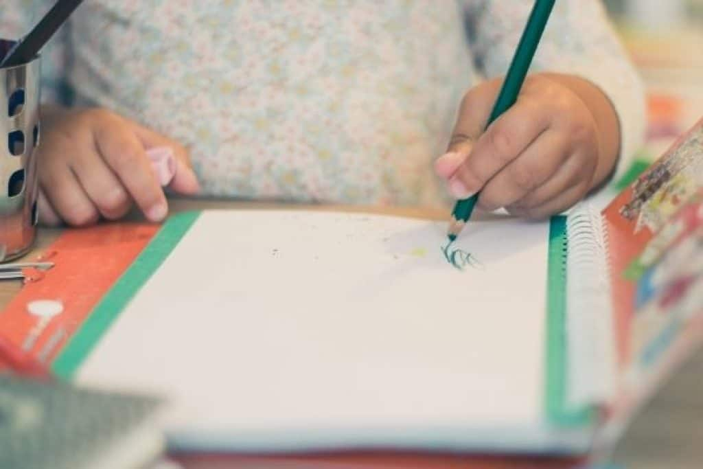 Left handed kid writing on paper with colored pencil
