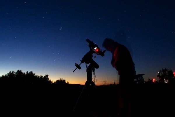 Person with computerized telescope at dawn