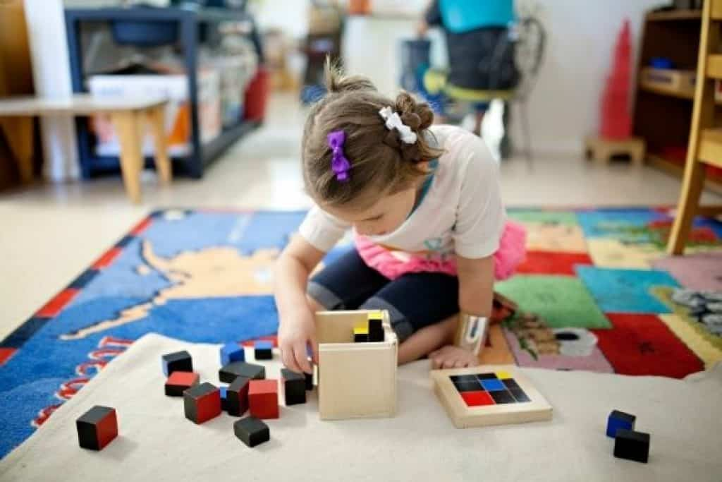 Young girl with educational wooden blocks