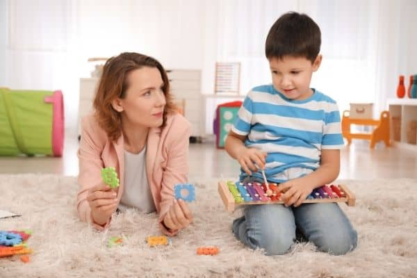 Parent and child with autism playing with shape and musical toys
