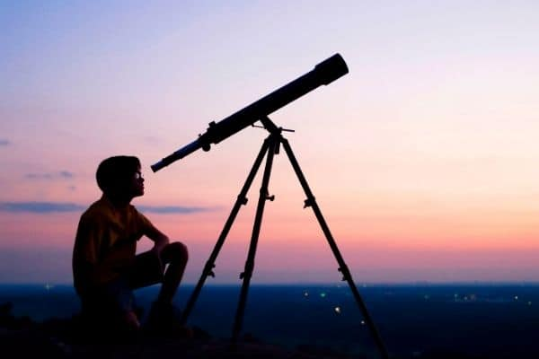 Young boy observing the sky with a telescope