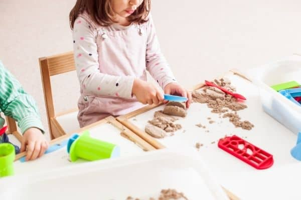 Children with sensory processing disorder playing with kinetic sand